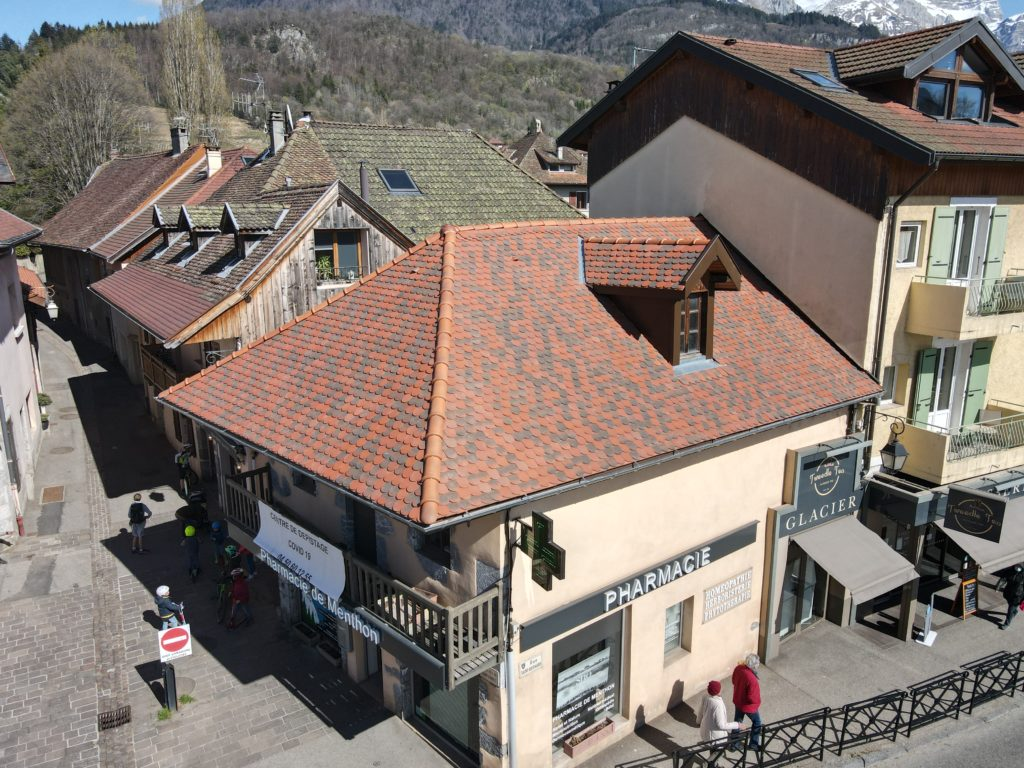 Rénovation de toiture traditionnelle couverture en tuile écaille de la pharmacie de Menthon Saint Bernard en Haute Savoie